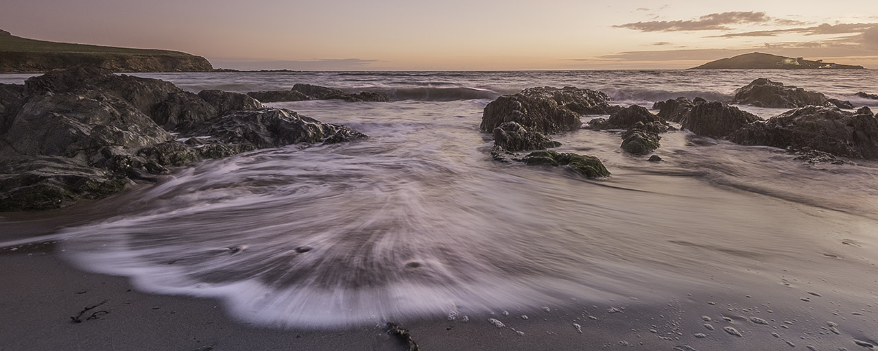 A long exposure seascape with water rushing over sand between the jagged rocks at sunset. Burgh Island can be seen on the horizon from this South Devon beach.